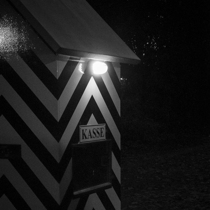 A hut with striped patterns and a light on at the parking lot entrance in düsseldorf kaiserswerth