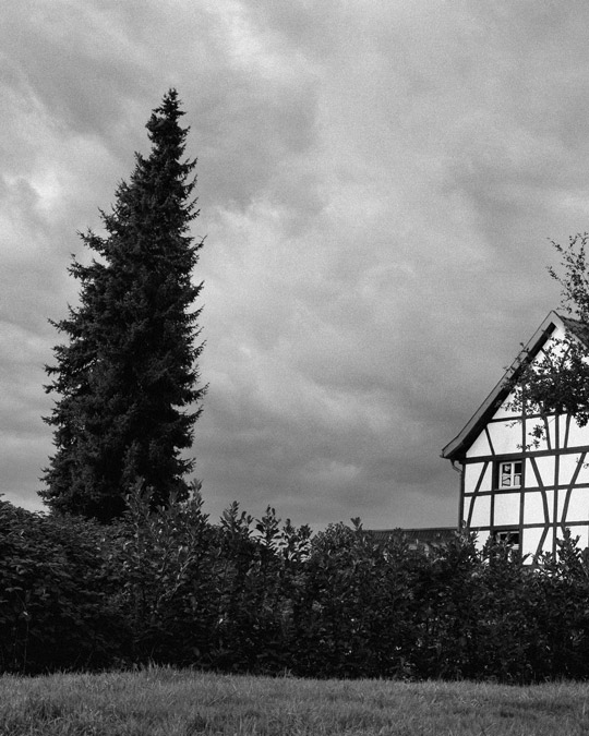 A traditional German farmhouse beside the trees in cloudy covered air Essen Baldeney