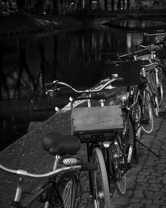 Old bicycles parked by the stream and tree reflections on the water Königsallee Düsseldorf